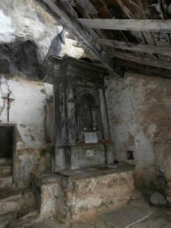 Puerta de la zona rupestre y altar de madera