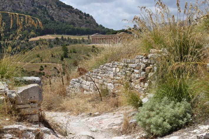 Camino de bajada desde el Teatro griego y con vistas al imponente Templo, Segesta, Sicilia (Italia)