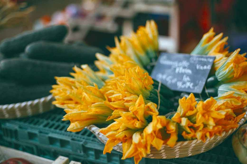 zucchini flowers with price at counter in market