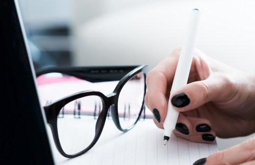 Bril en schrijvende vrouwenhand