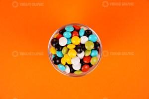 Chocolate coated peanuts in bowl on orange