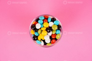 Chocolate coated peanuts in bowl on pink background