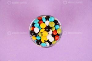 Chocolate coated peanuts in bowl on purple