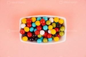 Chocolate coated peanuts on pink