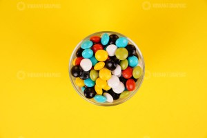 Chocolate drops in bowl on yellow