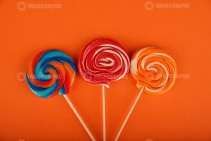 Spiral colored round lollipops on orange background