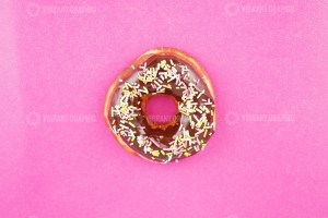 Chocolate donut with topping on pink background