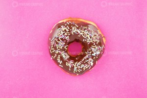 Delicious chocolate donut on pink background