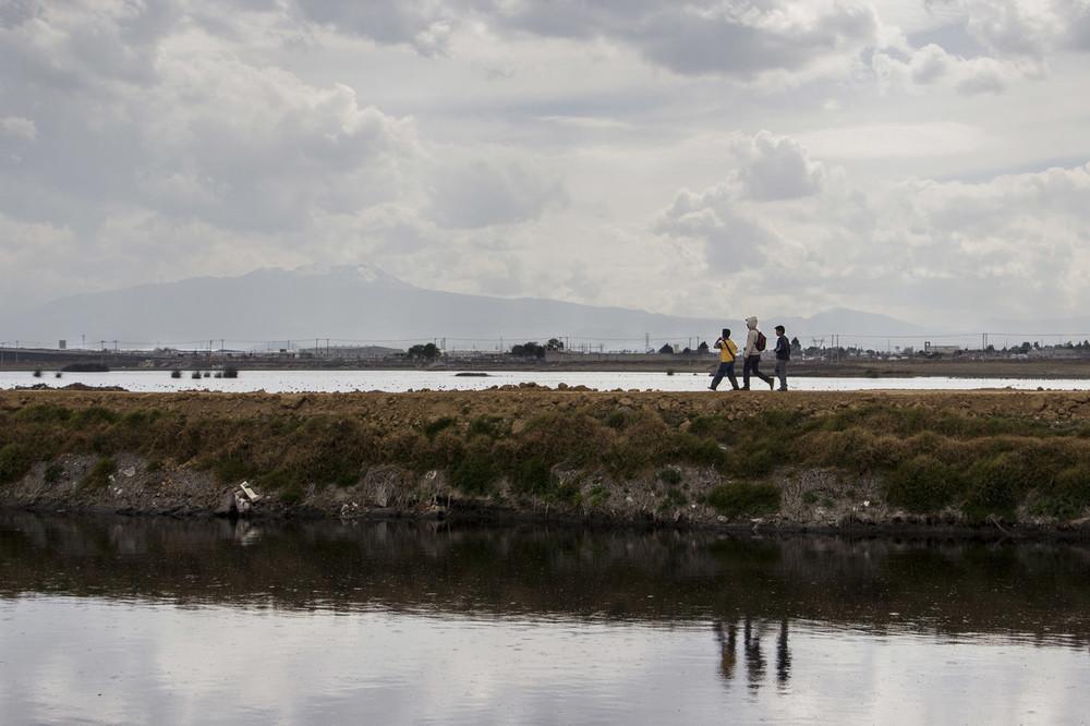 """Con el Xinanténcatl de fondo, niños caminan a orillas del Río Lerma. El camino que lleva al poblado """"El Cerrillo"""" es popular por el alto número de asaltos que ocurren en él."""