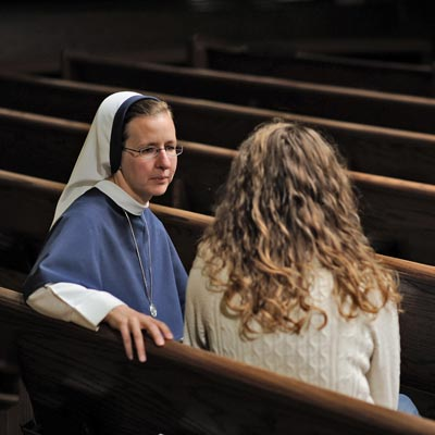 Photo of nun talking with young female student