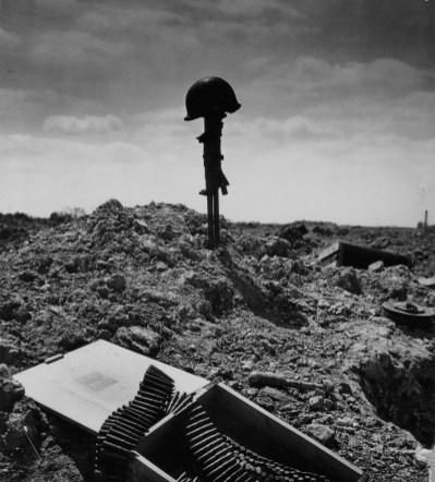 """Secteur Charlie, Le champ de bataille est jonché de petit matériel de guerre. Au premier plan une caisse à bandes de mitrailleuse et à droite un chargeur circulaire (type """" camembert """"). Au centre de la photo une Vickers K-Gun qui se dresse plantée en terre par le canon, coiffée du casque d'un Rangers américain dont il semble marquer la tombe provisoire. Pourquoi une arme britannique à cet endroit ? Le 6 juin pour l'assaut de la pointe du Hoc, 4 Dukw étaient équipés d'échelles (empruntées au London Fire Department), avec au sommet un affût spécial pour 2 Vickers-K-gun (et non de Lewis comme beaucoup le disent) Voir ici: http://www.flickr.com/photos/mlq/1179889170/ Un Dukw est prévu pour Dog, Easy et Fox Co chaque compagnie fournira le personnel pour """" son Dukw """" sauf le dernier dont l'équipage provient de toutes les unités. Lancés depuis le LCT(5) 413, seul 3 DUKW seront """"opérationnels"""" mais ne pourront s'approcher suite aux cratères et à l'affaissement d'une partie de la falaise, toutefois au moins un courageux Ranger le Sgt W Stivison grimpera sous le feu allemand pour utiliser les Vickers contre l'ennemi. Devant la Pointe du Hoc l'un d'entre eux le N°2 de la E Co est coulé par les tirs des armes légères et 20mm allemands à 06h40, malgré 3 blessés dont un grave (l'équipage complet d'un DUKW """"échelle"""" comprend: un chauffeur, un opérateur d'échelle, un tireur, 4 hommes) ils seront tous secourus. Serait-ce une de ces armes démontées quelques heures plus tard depuis un des DUKW ? Date et lieu exact inconnus. Compte tenu des objets présents (arme anglaise et casque de Rangers) la Pointe du Hoc est la localisation la plus vraisemblable. Montage réalisé par le photographe S. Scott Wigle (Coast Guard ) ou tombe provisoire ? Cette photo a inspiré des artistes: http://www.flickr.com/photos/mlq/2277045756/in/pool-autresphotosnormandie Voir également cet article de Patrick Peccatte : http://culturevisuelle.org/dejavu/346"""