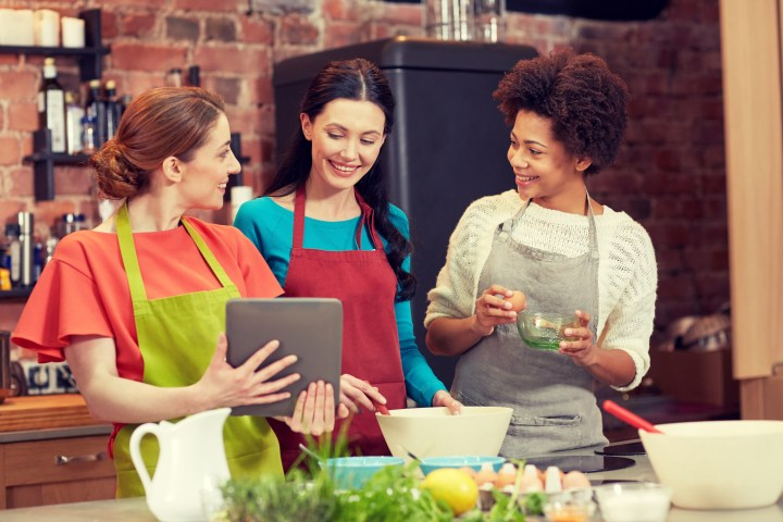 happy women with tablet pc cooking in kitchen