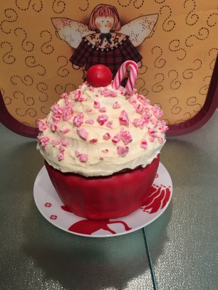 Cupcake cake with red fondant and a frosting with candy cane pieces for decoration