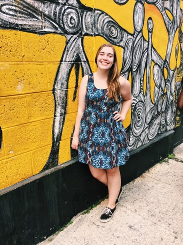 Standing in front of a bright yellow mural in Havana.