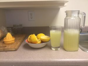 Lemons, Manual juicer, pitcher, tall clear glass.