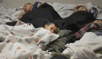 Detainees sleep in a holding cell at a U.S. Customs facility in Brownsville, Texas. Photo via Getty Images