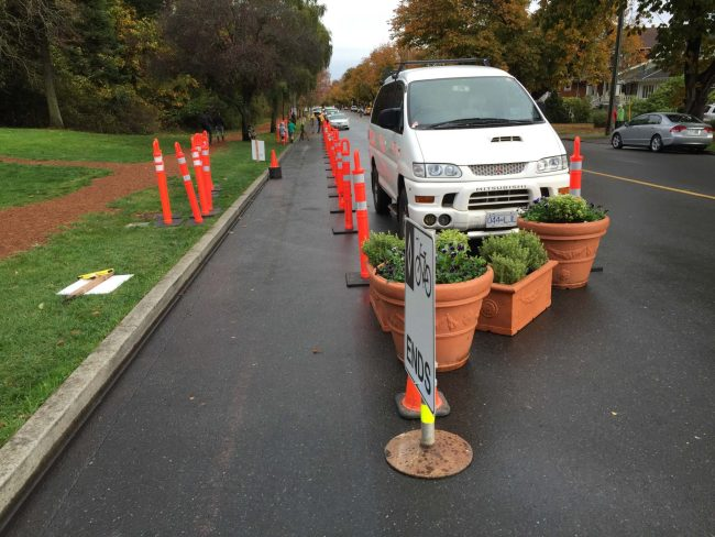 The parking-protected bike lane with temporary bollards and planters. No loss of parking, just narrowed driving lane.