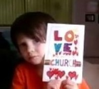 "Photo: Child Holding card they coloured that reads ""love is the Spirit of This Church"""