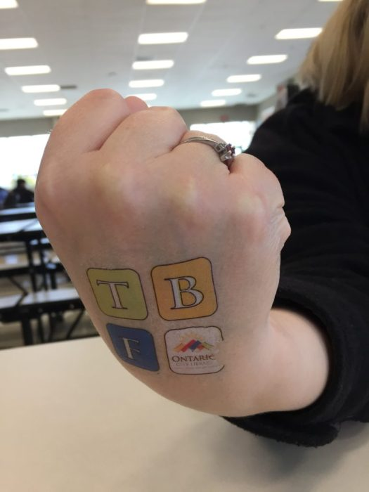 Image of a hand with a temporary tattoo of the OTBF logo.