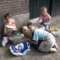 Ingeborg, Gaia en Dagmar lezen een stripboek op het plein