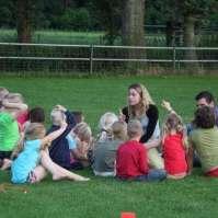 Roxanne en Roeland leggen een spel uit aan de jongere kinderen