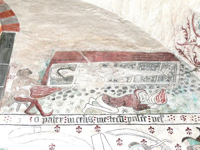 A medieval wall painting of St Lawrence tied to an iron grate over a fire. Two men blow on the fire with bellows.