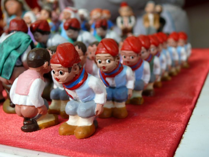 A photograph of rows of small figurines wearing red hats. They are crouching with their trousers pulled down.