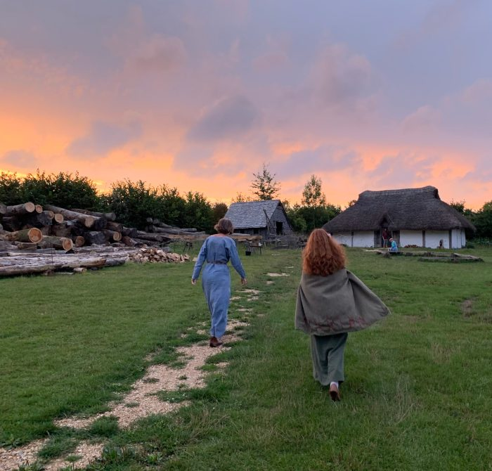 A photograph of two people in medieval women's clothing walking towards two small wooden houses at sunset.