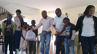 Handing over the foodstuff to the kids donated by staff of K-rep Bank Meru Branch