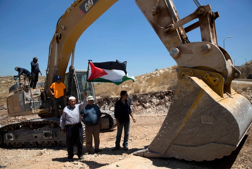 Palestinians demonstrate in front of Israeli bulldozers that were bulldozing land outside Deir Qaddis village near Ramallah for an apparent plan to expand a nearby Jewish settlement. (AP)