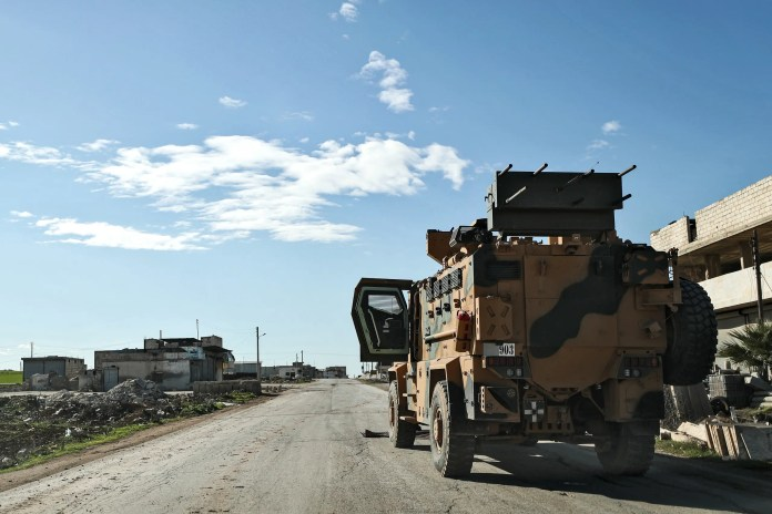 Turkish military vehicles at a checkpoint on the eastern outskirts of Saraqib on Saturday (AFP)