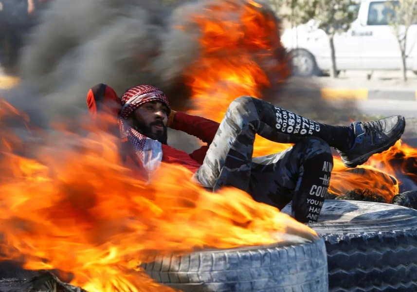 An Iraqi demonstrator sits amid burning tires blocking a road during ongoing anti-government protests in Najaf, Iraq February 2, 2020. (Photo: Reuters)