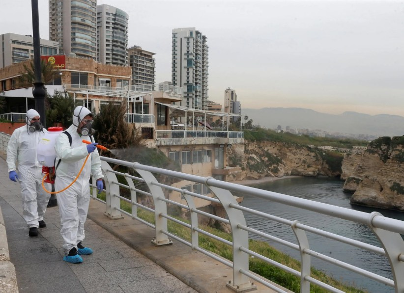Employees from a disinfection company sanitize handrails, as a precaution against the spread of the coronavirus, at Beirut's seaside Corniche, on March 5, 2020. (Reuters)