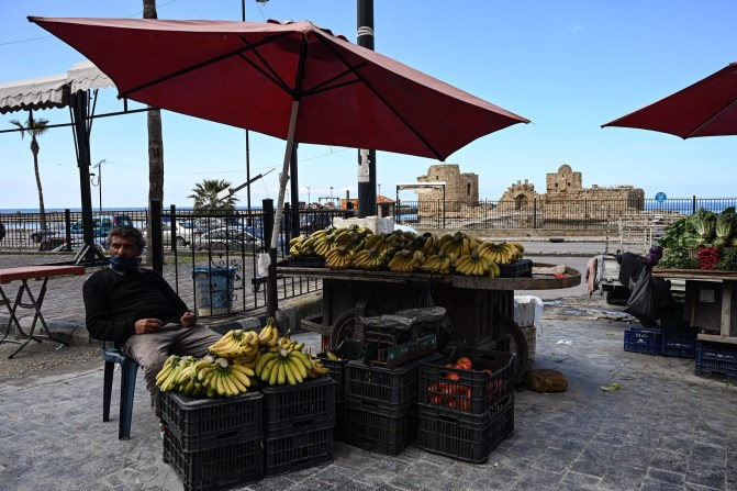 A fruit vendor waits for customers at his stall in front of Sidon's sea castle during a nationwide lockdown implemented to slow the spread of coronavirus. (Finbar Anderson)