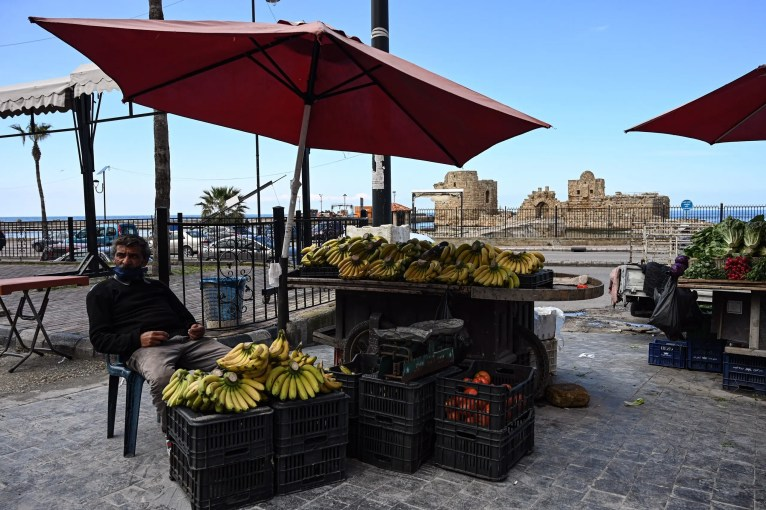 A fruit vendor waits for customers at his stall in front of Sidon's sea castle. (Finbar Anderson)