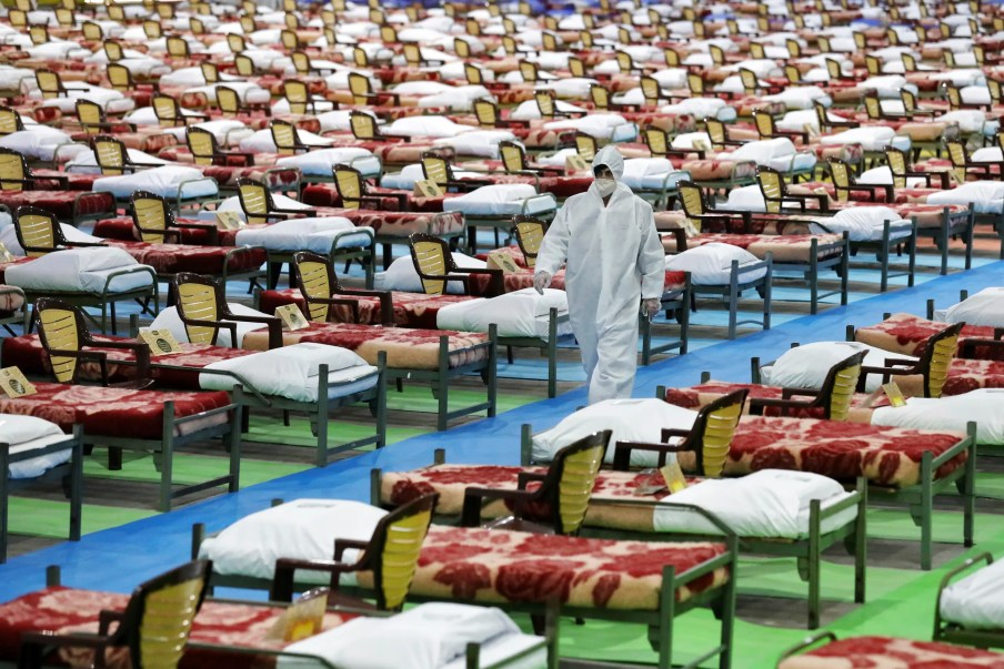 People in protective clothing walk past rows of beds at a temporary 2,000-bed hospital for COVID-19 coronavirus patients set up by the Iranian army at the international exhibition center in northern Tehran, Iran, on Thursday, March 26, 2020. (AP)