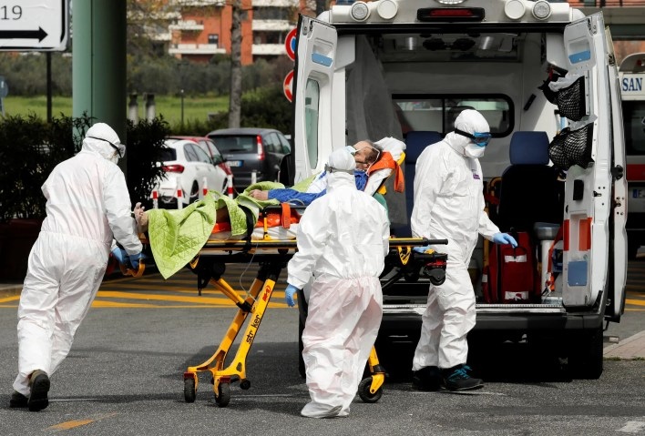 أفراد في الرعاية الصحية ينقلون مريضا بفيروس كورونا في روما