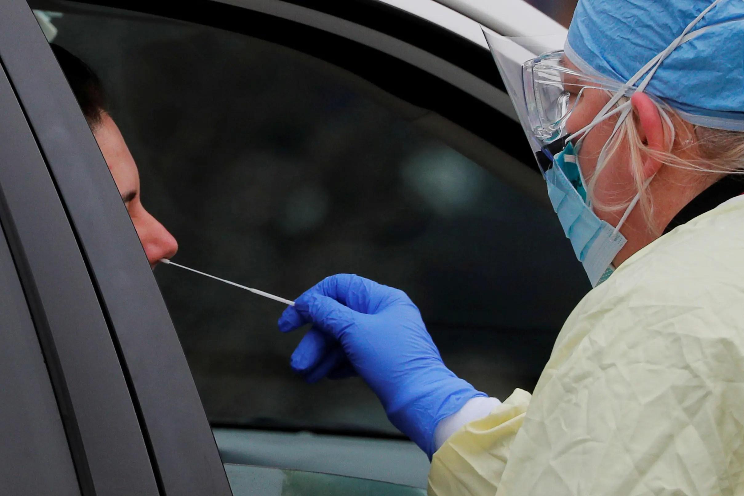 أحد العاملين بالرعاية الصحية يحصل على عينة لتحليلها في ميدفورد بولاية ماساشوستس الأميركية يوم 4 أبريل (من رويترز)