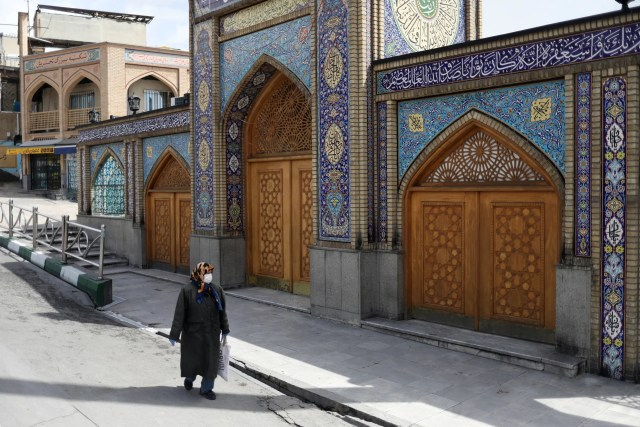 A woman wearing a protective face mask and gloves walks past the Imamzadeh Saleh shrine, amid fear of the coronavirus disease (COVID-19), in Tehran, Iran April 2, 2020. (Reuters)
