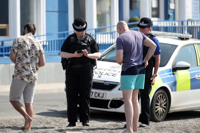 Two policewomen speak to two men who did not respect the closure in Wales, UK, and were playing on the beach