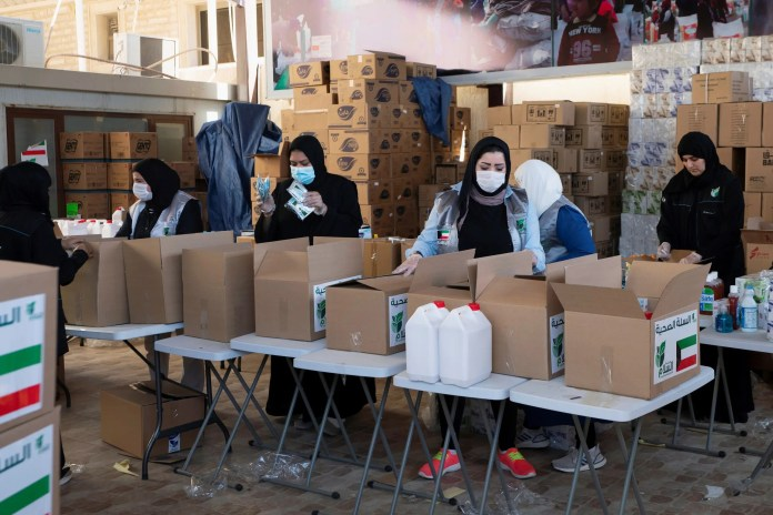 Kuwaiti volunteers distribute food to the most destitute due to the Corona crisis