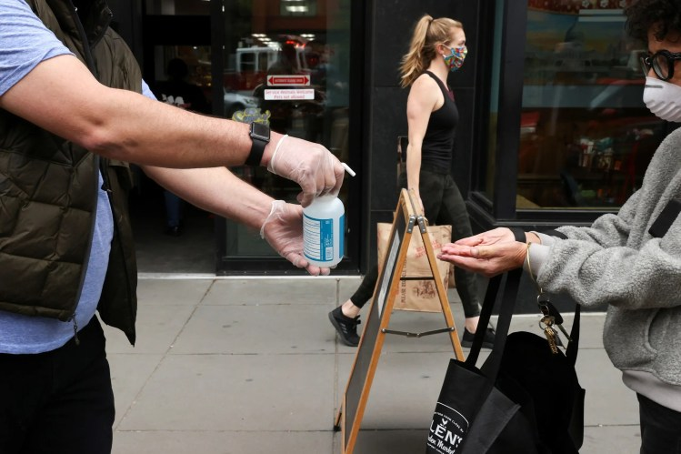 A store worker offers hand sanitizer to shoppers, during the coronavirus disease (COVID-19) outbreak, as they wait in line on the sidewalk outside a grocery store in Washington on April 14, 2020. (Reuters)