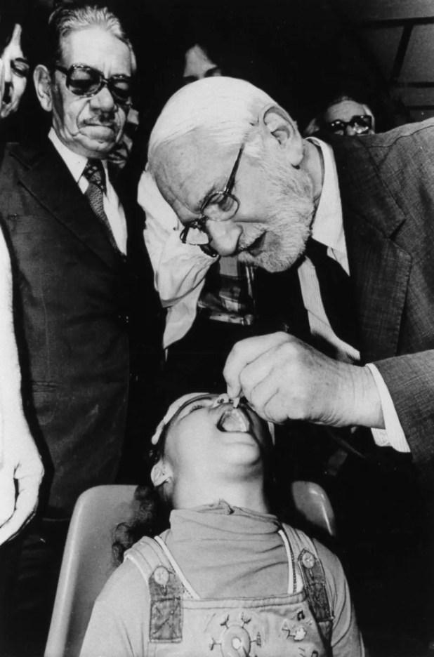 ألبرت بروس سابين أثناء تقديمه التلقيح الفموي ضد الشلل لأحد الأطفال