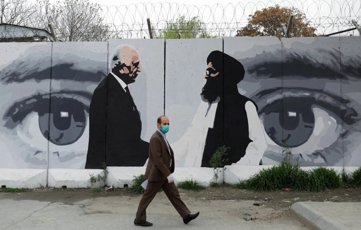 An Afghan man wearing a protective face mask walks past a wall painted with photo of Zalmay Khalilzad, U.S. envoy for peace in Afghanistan, and Mullah Abdul Ghani Baradar, the leader of the Taliban delegation, in Kabul, Afghanistan on April 13, 2020. (Reuters)