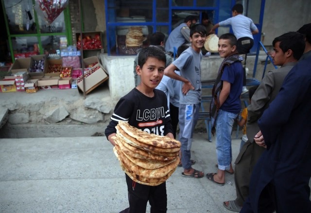 A young boy receives free bread from the municipality during a lockdown aimed at curbing the spread of the coronavirus, in the holy month of Ramadan in Kabul, on Monday, May 4, 2020. (AP)