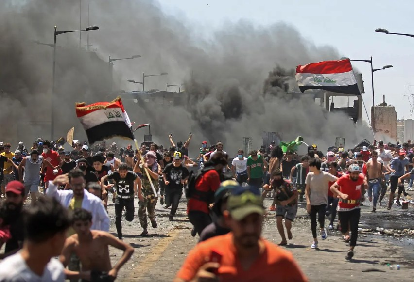 Iraqi protesters run for cover as they clash with security forces on Al-Jumhuriyah bridge in the capital Baghdad, during an anti-government demonstration on May 10,2020. (AFP)