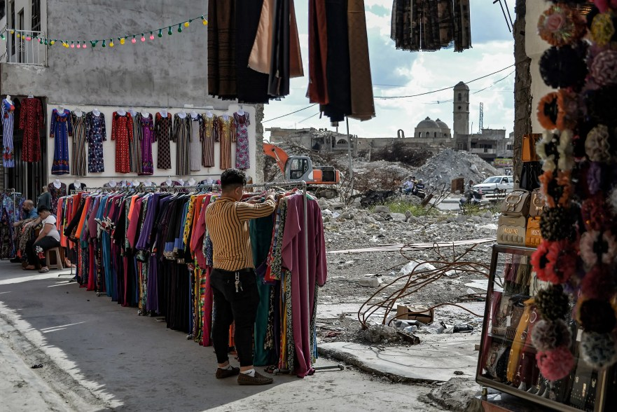 A seller arranges clothes put on display at the Sarj Khaneh market area in the old city of Iraq's northern Mosul, while the damaged Roman Catholic Church of Our Lady of the Hour is seen in the background, on May 3, 2020. (AFP)