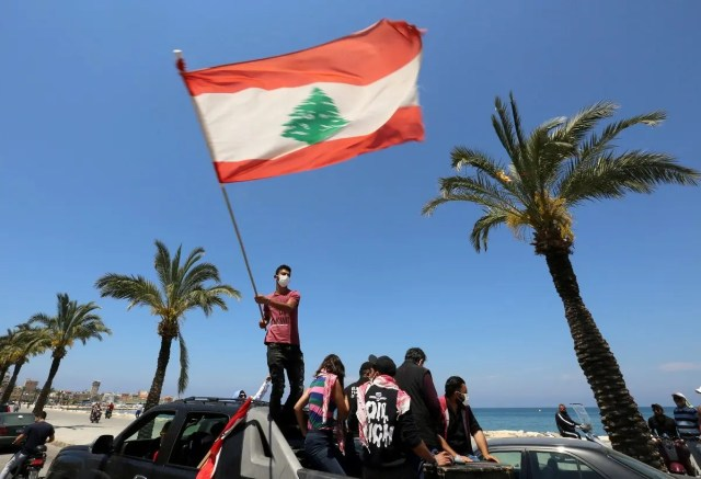 A demonstrator, wearing a mask as a preventive measure against the spread of coronavirus disease waves a national flag during a protest in cars against the growing economic hardship and to mark Labor Day in Tyre, Lebanon May 1, 2020. (Reuters)