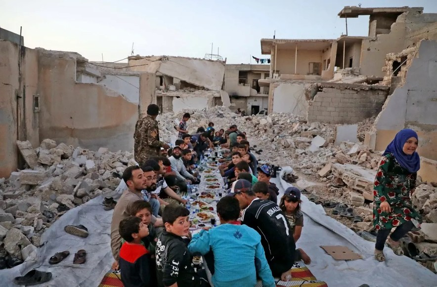"This picture taken on May 12, 2020 in the village of Kafr Nuran in the western countryside of Syria's northern Aleppo province shows men and children seated together in the midst of ruins before starting the ""iftar"" fast-breaking meal. (AFP)"