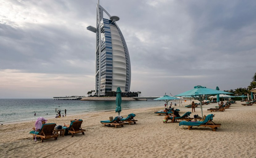Beach-goers lie on lounge chairs by the shoreline near the Burj al-Arab hotel in Dubai, UAE on May 20, 2020. (AFP)